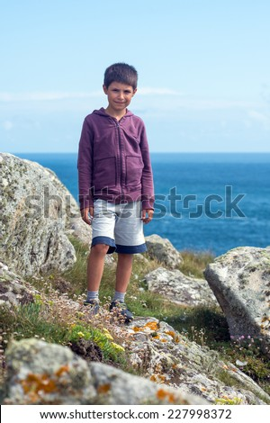 Young kid portrait climbing cliff in the coast of Brittany, France. - stock photo