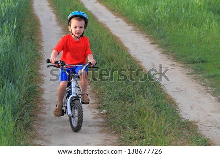 Young kid riding his bike on a green field - stock photo