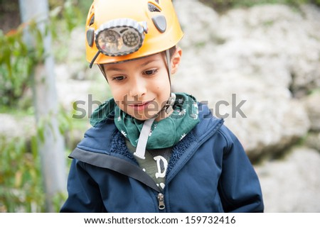 Young kid wearing helmet for cave exploration.  - stock photo