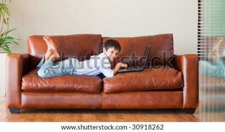 Young kid with a laptop on the couch - stock photo