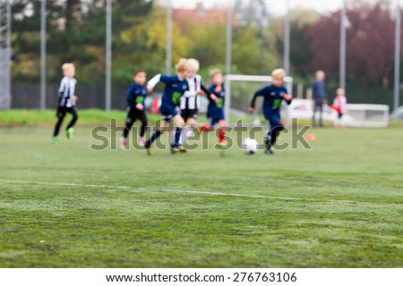 Young kids during a boys soccer match on green soccer pitch. - stock photo