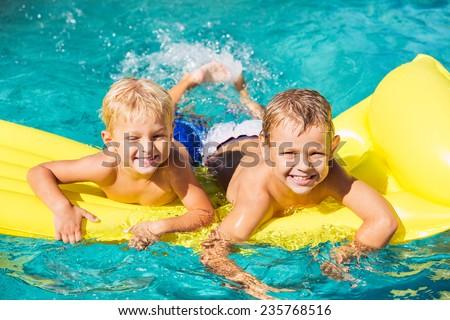 Young Kids Having Fun in Swimming Pool on Yellow Raft. Summer Vacation Fun.   - stock photo