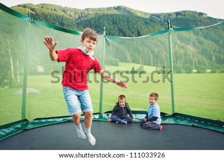 Young kids jumping in mountain scenery. - stock photo
