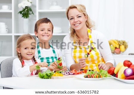 Young kids with their mother in the kitchen - preparing a healthy vegetables snack