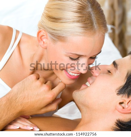 Young kissing cheerful attractive couple on bed - stock photo
