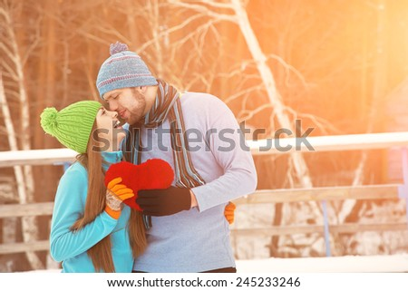 Young kissing couple in love outdoors in the winter with a red heart in hands - stock photo