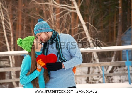 Young kissing couple in love outdoors in the winter with a red heart in hands. valentine's day - stock photo