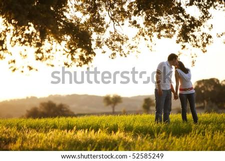 Young kissing couple on idyllic background - stock photo