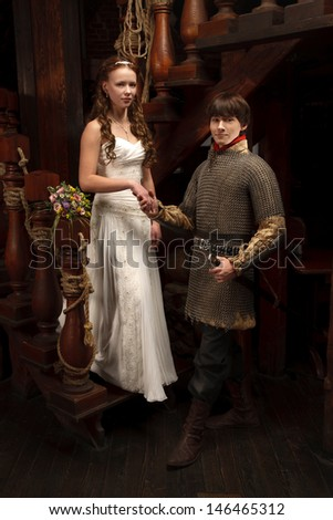Young knight and his bride standing on the wood ladder - stock photo