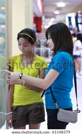 young ladies enjoying shopping at a mall - stock photo