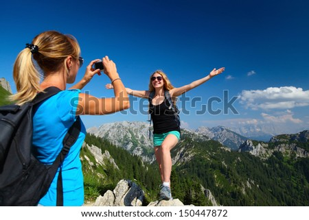 Young ladies with backpacks taking a pictures with Alps on the background - stock photo