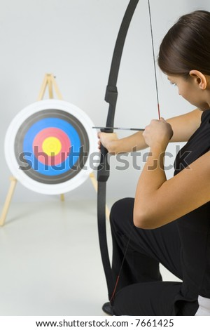 Young lady archer holding bow and taking aim at targer. Rear view - stock photo