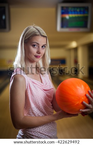 young lady at the bowling alley with the ball in hand, getting ready for the game of bowling
