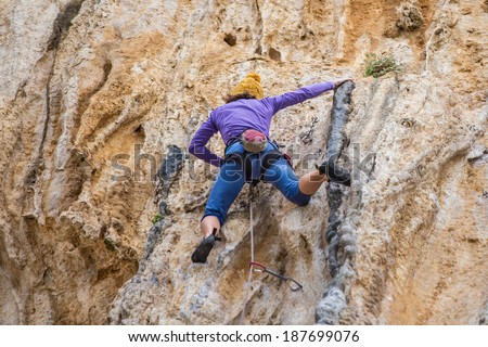 Young lady climbs in a rocks - stock photo