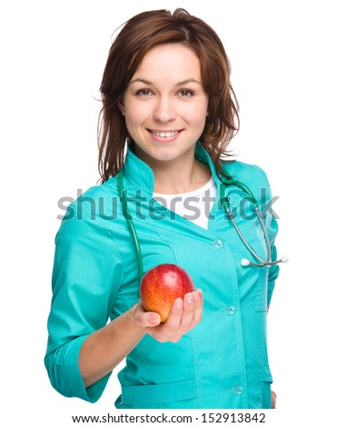 Young lady doctor is holding a red apple, isolated over white
