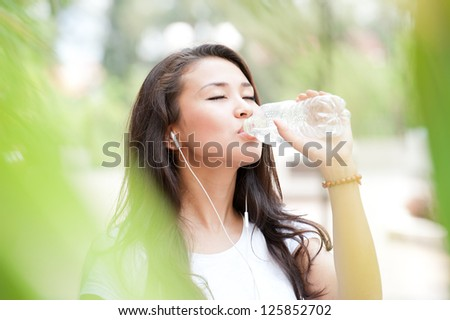 Young lady drinking water from the bottle
