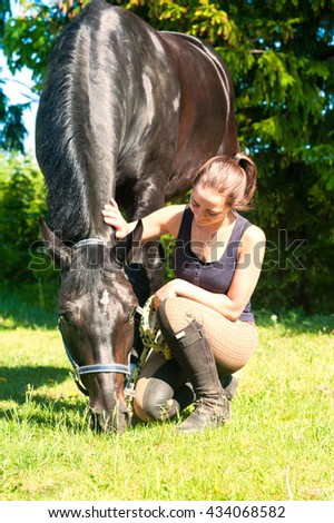 Young lady equestrian sitting and stoking her dark horse on green grass. Vibrant multicolored summertime outdoors vertical image. - stock photo