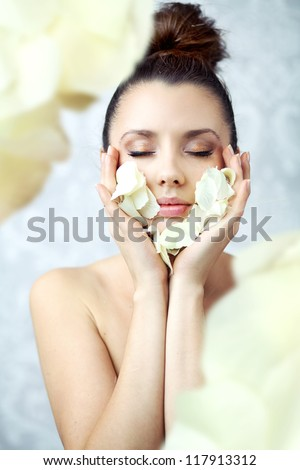 Young lady holding rose petals - stock photo