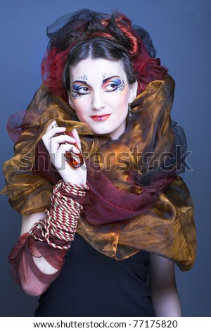 Young lady in artistic image with perfume bottle in her hands - stock photo