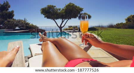 Young lady in bikini holding orange juice glass while sitting on a lounge chair along the poolside on a sunny day. Panorama view. - stock photo