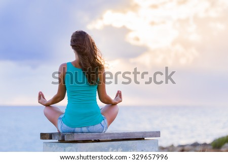 Young lady in yoga meditation pose sitting on a bench at the Mediterranean sea at sundown. - stock photo