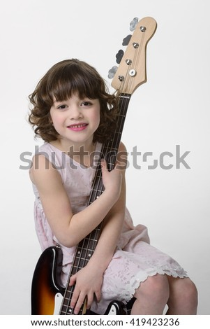 Young lady is embracing the bass guitar with her tender childish hands and looks in the camera with lovely smile. Close-up portrait of caucasian kid with true positive emotions. - stock photo