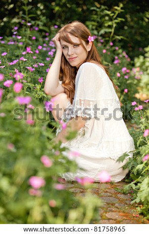 Young lady is surrounded by summer flowers
