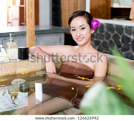 Young lady lying in bath - stock photo