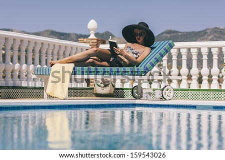 Young lady on sun lounger relaxing by the pool reading a book in a wide brimmed hat - stock photo
