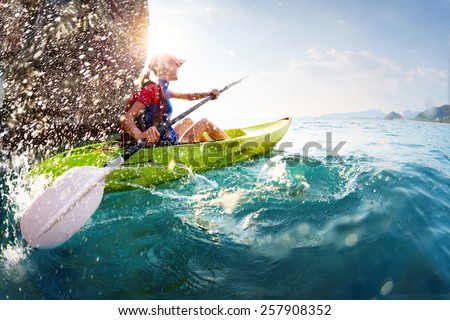 Young lady paddling hard the kayak with lots of splashes near the cliff at sunny day - stock photo