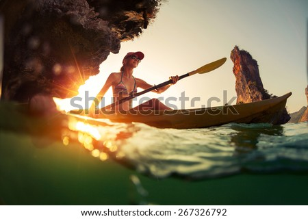 Young lady paddling the kayak in a bay with limestone mountains. Split shot with underwater view at sunset - stock photo
