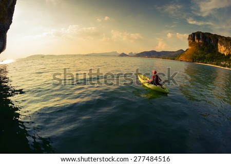 Young lady paddling the kayak in a calm lagoon - stock photo
