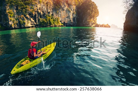Young lady paddling the kayak in the calm bay with limestone mountains - stock photo