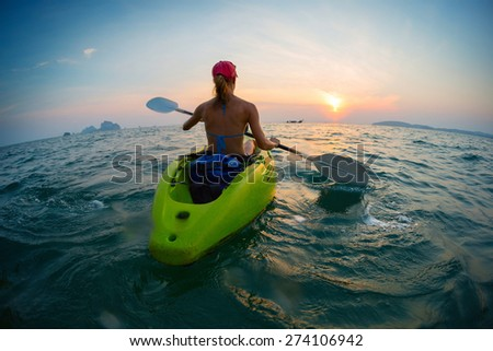 Young lady paddling the kayak in the open calm sea at sunset - stock photo