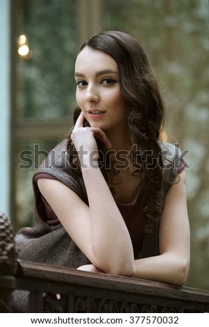 young lady posing in fashion dress on balcony