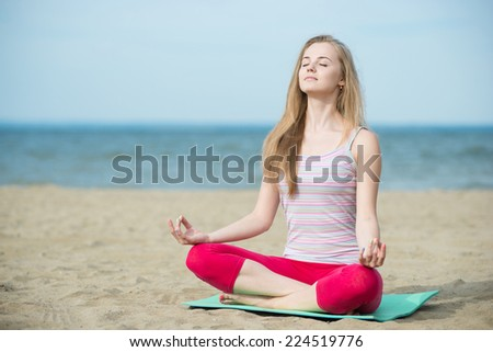 Young lady practicing yoga. Beautiful woman posing at sand beach. Workout near ocean sea coast. Beautiful fit tan girl. Fitness model caucasian ethnicity outdoors. Weight loss exercise. Meditation. - stock photo