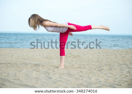 Young lady practicing yoga. Beautiful woman posing at the summer sand beach. Workout near ocean sea coast. Beautiful fit tan girl. Fitness model caucasian ethnicity outdoors. Weight loss exercise - stock photo