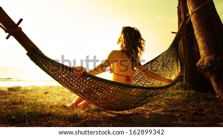Young lady relaxing in hammock on the tropical beach at sunset - stock photo