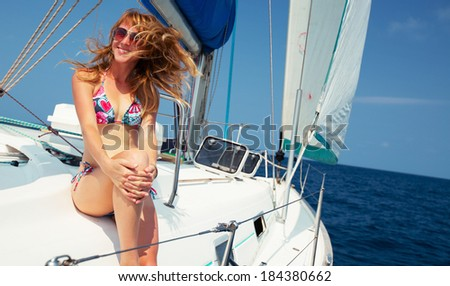 Young lady relaxing on the sail boat in the tropical sea at sunny day - stock photo