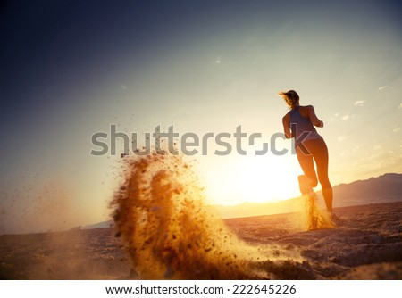 Young lady running in a desert at sunset - stock photo
