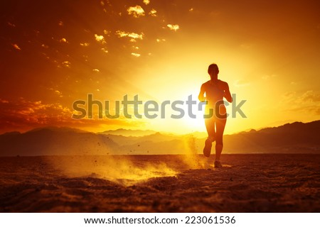 Young lady running in the desert at sunset - stock photo