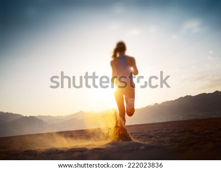 Young lady running in the desert at sunset. Edges are blurred focus on the feet