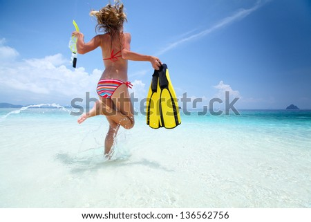 Young lady running into tropical sea with snorkeling equipment at sunny day
