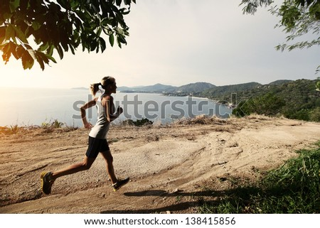 Young lady running on a rural road - stock photo