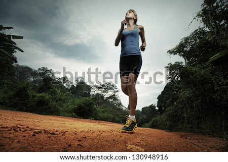 Young lady running on cross country road with earphones - stock photo