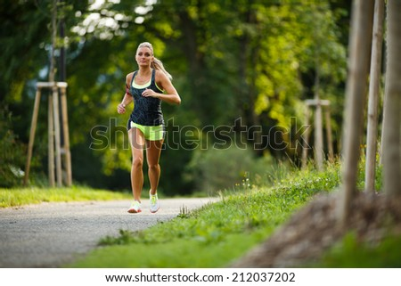 Young lady running. Woman runner running through the spring park road. Workout in a Park. Beautiful fit Girl. Fitness model outdoors. Weight Loss - stock photo