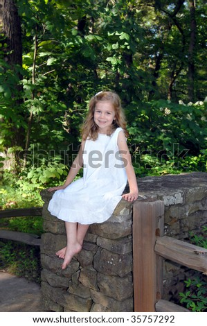 Young lady sits on a rustic stone wall in the Birmingham Botanical Garden in Birmingham, Alabama.  She is wearing a white eyelet dress and smiling, happily. - stock photo