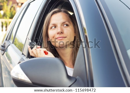 Young lady sitting in a car and showing key - stock photo