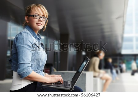 Young lady sitting in a modern cityscape with laptop - stock photo