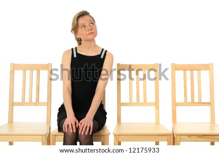 Young lady sitting on a chair and waiting, looking up. - stock photo